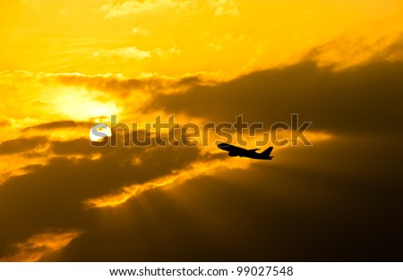 Silhouette of small commercial airplane against orange and cloudy sky