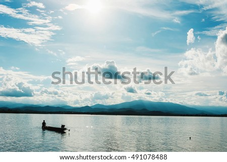 silhouette of small fishing boat in the lake with mountain view against cloudy sky at sunset