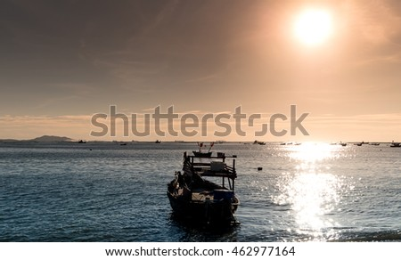 Silhouette of Small Ships in The Sea at Twilight Time with Beautiful Sun and Reflection at Chonburi, Thailand