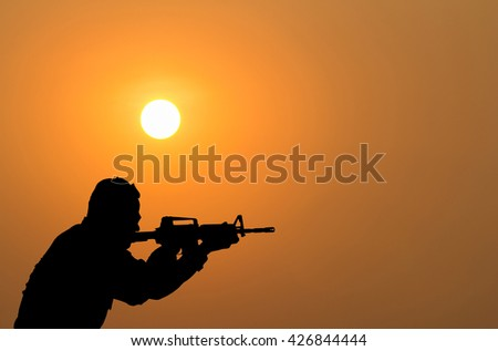 silhouette of sodier shootimg gun on sunset.