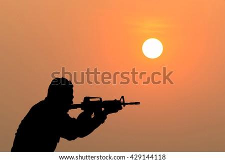 silhouette of sodier shootimg gun on sunset. - stock photo