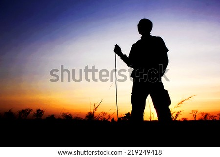 Silhouette of soldier against a sunset - stock photo