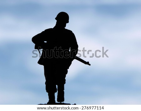 Silhouette of soldier against sky     - stock photo