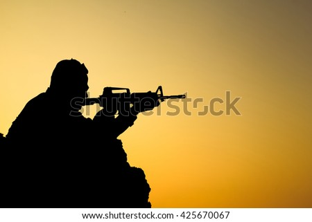 silhouette of soldier shooting gun on sunset.