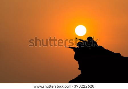 silhouette of soldier shooting with his weapon  on sunset. - stock photo