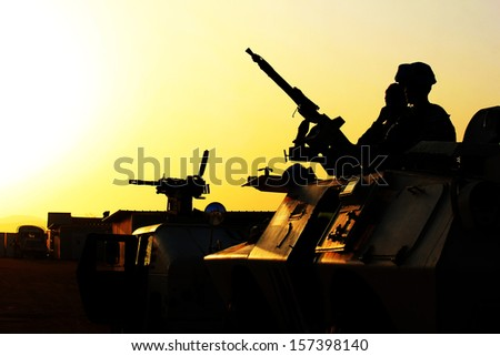 Silhouette of soldier with machine gun on a car against a sunset - stock photo