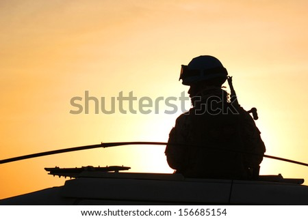 Silhouette of soldier with rifle on a car against a sunset - stock photo