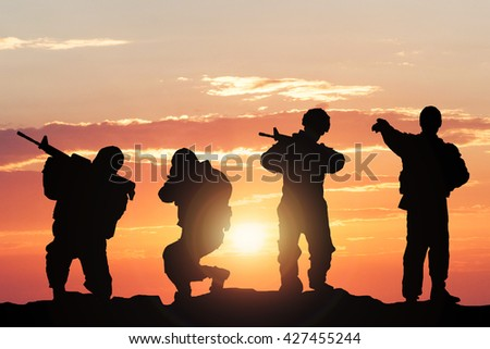 Silhouette Of Soldiers Armed With Weapons Against Climatic Sky On Battlefield
