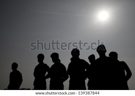 Silhouette of soldiers line up against the sun. - stock photo