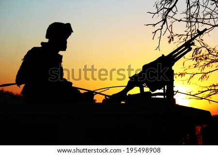 Silhouette of soldiers with a machine gun on the vehicle and radio communication in hand. - stock photo