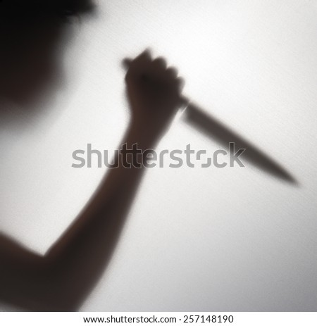 Silhouette of someone holding knife,blur image