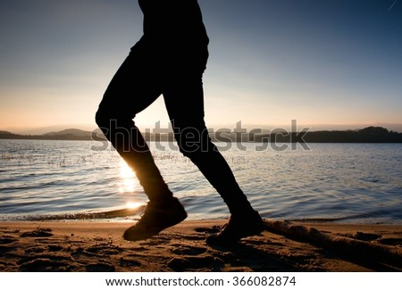 Silhouette of sport active man running and exercising on coastline at sunset.