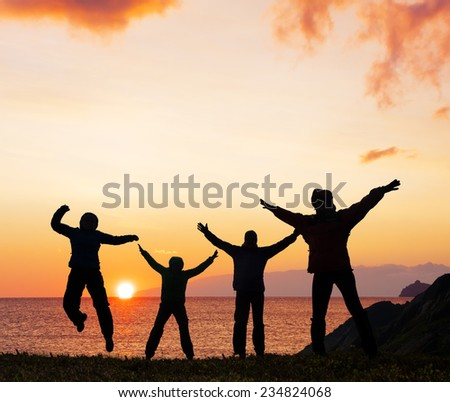 Silhouette of sport  friends on beach jumping - stock photo