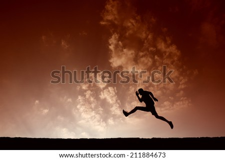 Silhouette of sport man jumping with blue sky and clouds on background