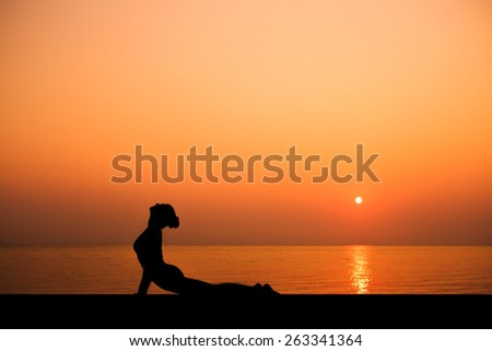 Silhouette of sport slim woman making yoga poses on the beach with Seaview in sunset