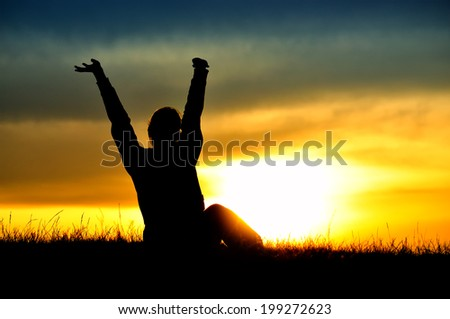 Silhouette of standing woman with rising hands, sunset sky as a