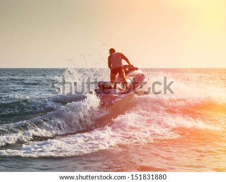 Silhouette of strong man jumps on the jetski above the water at sunset - stock photo