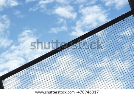 Silhouette of Structure mesh metal fence on sky background