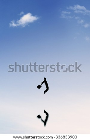Silhouette of successful businessman holding a suitcase and jumping on the sky with reflection of his shadow - stock photo