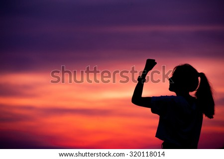 silhouette of Successful woman with arm up. - stock photo