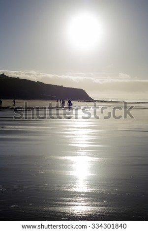 silhouette of surfer and people out for a walk as the sun sets in Ballybunion county Kerry Ireland - stock photo