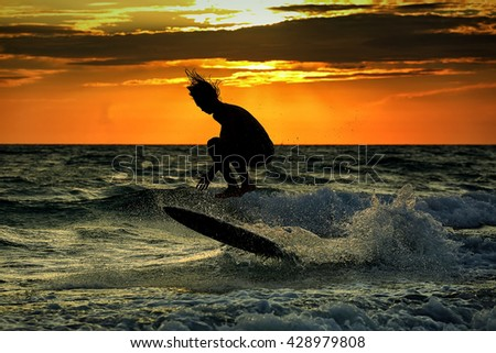 Silhouette of surfer at sunset Unrecognizable face. - stock photo