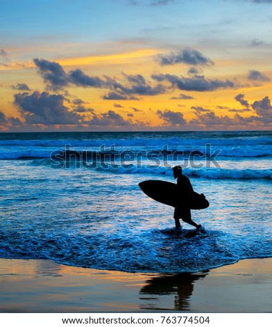 Silhouette of surfer on the beach with surfboard at sunset. Bali island