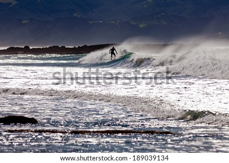 Silhouette of surfer riding big ocean wave on surfboard as it starts to break with spray flying - stock photo