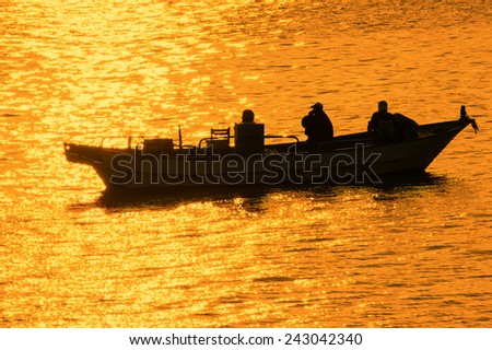 Silhouette of Taiwan Fishing Boat Bathed in Golden Glitters on Wavy Water. Some Fishermen Make a Living by Small Boats Near The Coasts of Kaohsiung, Taiwan  - stock photo