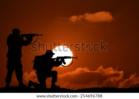 Silhouette of team soldier or officer with weapons at sunset - stock photo
