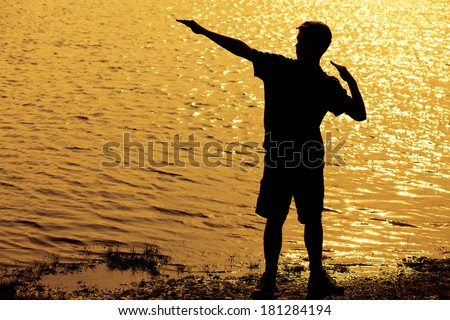 Silhouette of teenage boy striking a cool pose with arms up  - stock photo