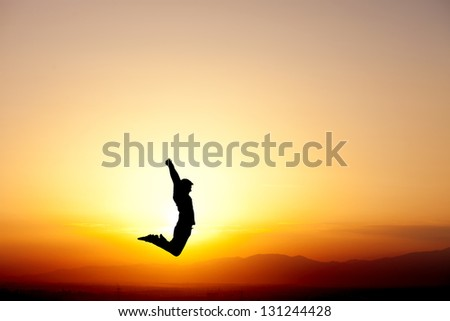 silhouette of teenager jumping in sunset for fun - stock photo