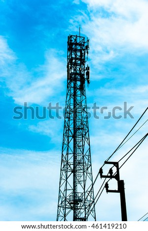 Silhouette of telecommunication tower with blue sky and white clouds.