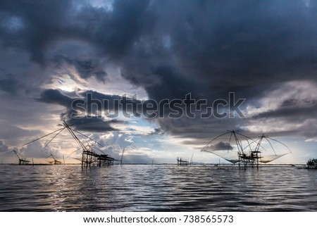 Silhouette of Thai southern fishing tool fishing industry of traditional Thai people Phatthalung Province.Sky with rain clouds as background.