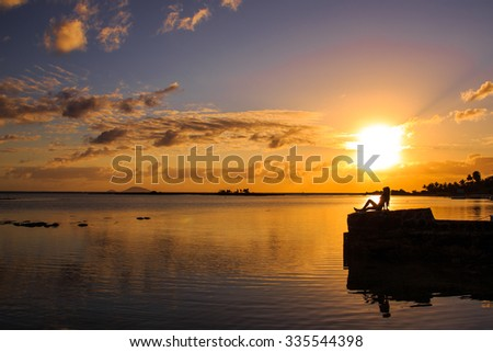 Silhouette of the beautiful girl sitting on a beach watching sunrise or sunrise