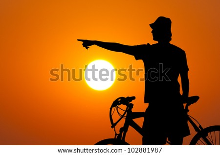 Silhouette of the bicycle rider against sun and orange sky showing something in the distance.