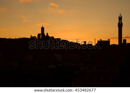 silhouette of the city of Siena at sunset with red and orange sky and the profile of the tower and marble duomo