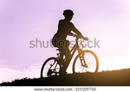 Silhouette of the cyclist riding a mountain bike. - stock photo