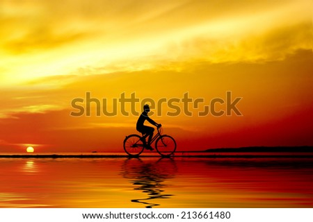 silhouette of the cyclist riding at sunset with reflection - stock photo