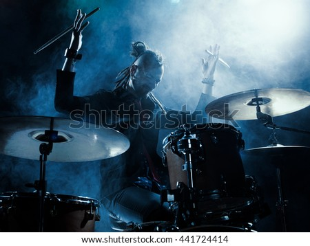 Silhouette of the drummer on stage. Dark background, smoke, spotlights - stock photo
