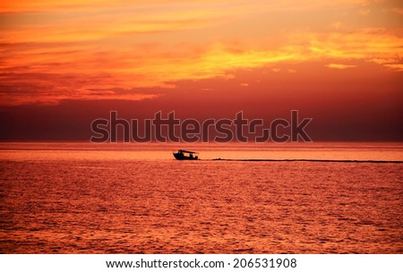 Silhouette of the fisherman or leisure boat sailing after golden sunset with saturated sky and clouds. Beautiful seascape in the evening. Harmony with nature idea. Tranquility and freedom background. - stock photo