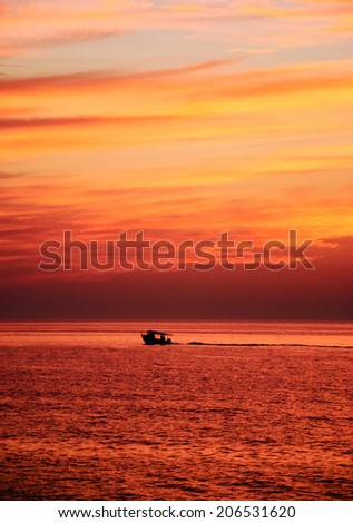Silhouette of the fisherman or leisure boat sailing at golden sunset with saturated sky and clouds. Beautiful seascape in the evening. Harmony with nature idea. Tranquility and freedom background. - stock photo