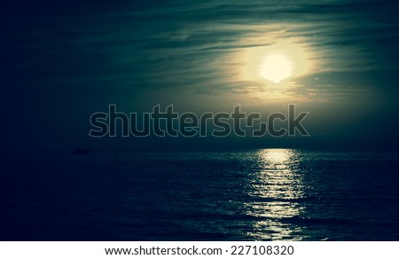 Silhouette of the fisherman or leisure boat sailing toward the moon. Dark sky and clouds. Moonwalk. Reflection in water. Beautiful seascape in the night. Harmony with nature idea. Mystery background. - stock photo