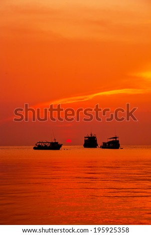 Silhouette of the fishing boats in the sunset sky