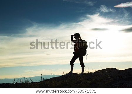 Silhouette of the girl looking in a distance against a decline