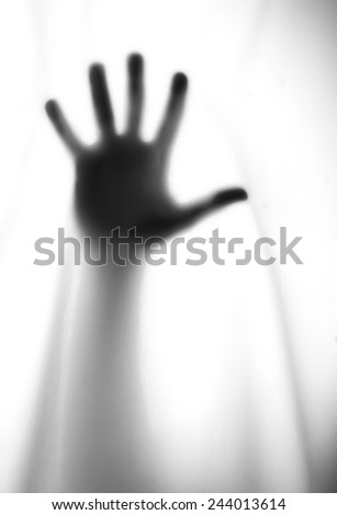 silhouette of the hand behind a transparent cloth