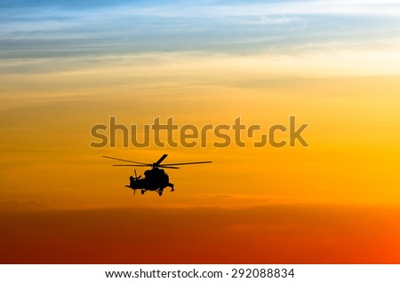 silhouette of the helicopter at sunset - stock photo