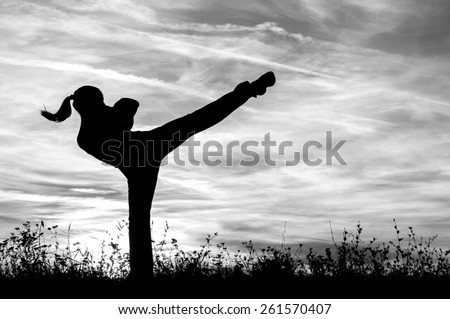 Silhouette of the kickboxing girl exercising outdoor at sunset.