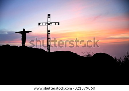 Silhouette of the man and ross on the top of the hill during colorful summer sunset. Man is thanksgiving to god. - stock photo