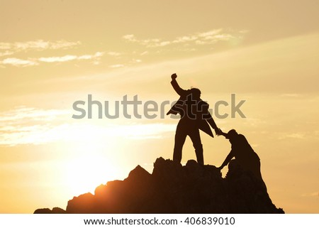 Silhouette of the man Bring hand up a friend to top the peak of mountain on sunrise sky , Business success goal together, Conceptual design. - stock photo